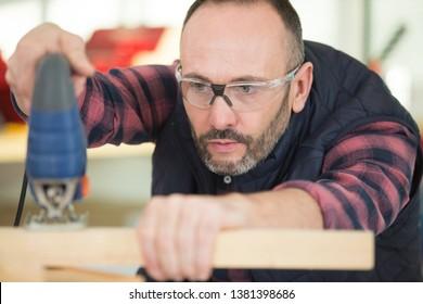 man using electric jigsaw to cut pine timber