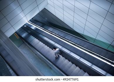 a man using escalator in a train station. blur slow speed shutter effect.