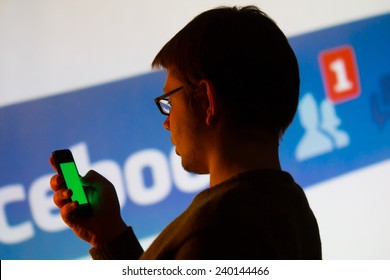 Man using Facebook application on his smartphone, background is a image from the projector - photography from social media meeting in city of Lodz, Poland 07.11. 2014