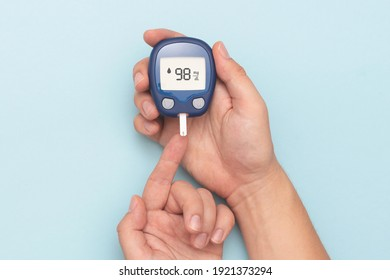 Man using glucometer, checking blood sugar level. Diabetes concept on blue background