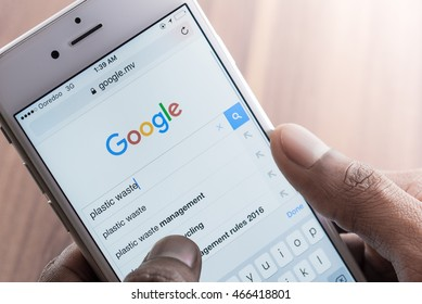 Man using Google Web Search on Smart Phone. Photo of iPhone with a Google search app running