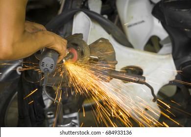 A man using grinder machine while repairing motorcycle engine