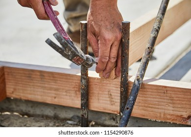 Man using a hammer and nail to  to fasten in a cement form board with shallow depth of field