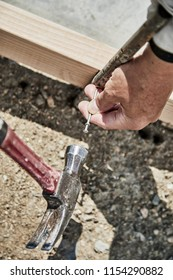 Man using a  hammer and nail to fasten in a cement form stake with shallow depth of field