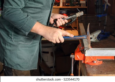 Man is using a hammer at welding work