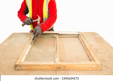 Man using a hammer while repairing and restoring an old window frame sash.