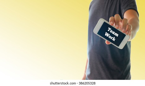 a man using hand holding the smartphone with text team work on display