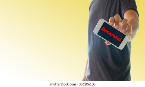 a man using hand holding the smartphone with text Becareful on display