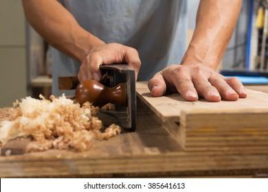 Man using hand plane in workshop