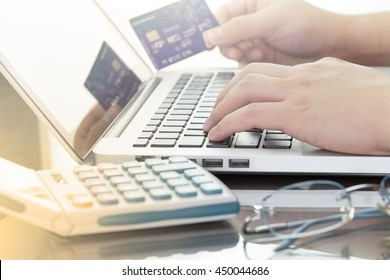 A man using his computer laptop and holding credit card intent to shopping online concept, digital business or e-commerce with calculator and glasses. warm tone.