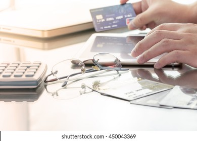 Man using his digital tablet while holding a credit card intent to online shopping, concept with digital business or e-commerce concept. close up, warm tone.