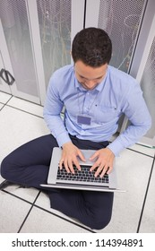 Man using his laptop in data center in front of servers