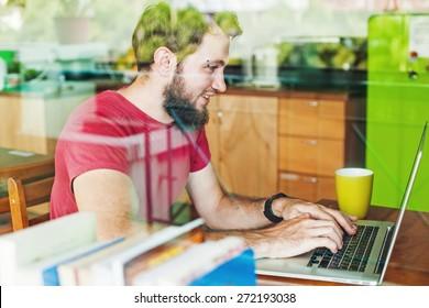 man using his laptop - view through the window