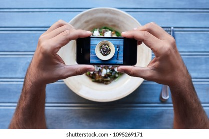 Man using his smartphone display to frame a picture of his delicious mixed organic salad while sitting at a bistro table