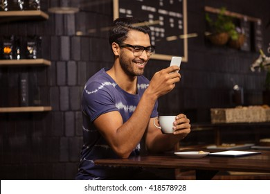 Man using his smartphone and drinking coffee in a coffee shop