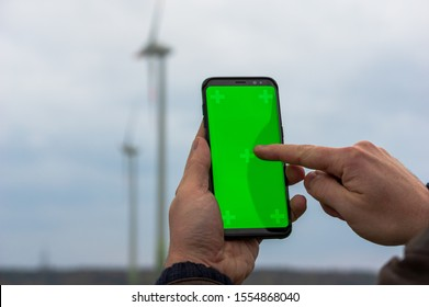 man using his smartphone in front of out of focus wind turbines. Accessing iot wind energy network with a cell phone. Using mobile phone outdoors in front of windpark. selective focus.