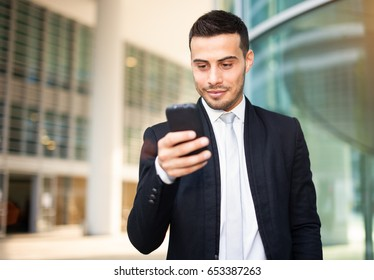 Man using his smartphone in modern business environment