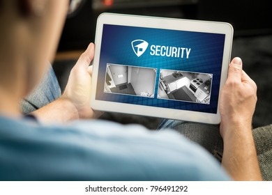 Man using home security system and application in tablet. Watching protection camera live footage inside a house or apartment. Smart cctv and safety app.
