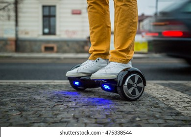 man is using hoverboard against the background of leaving car