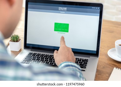 Man using internet banking website transfering money online with successful transaction message showing on laptop computer screen