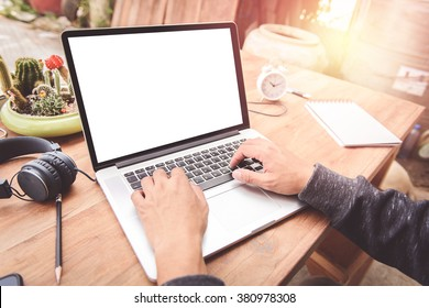 Man using the labtop on a desk outdoors. One corner of the house With the morning light
