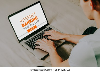 Man using a laptop computer to access to internet bank while sitting at home.