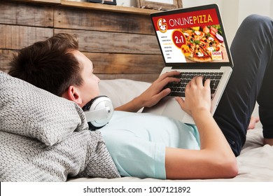 Man using a laptop computer to order pizza by internet at home.