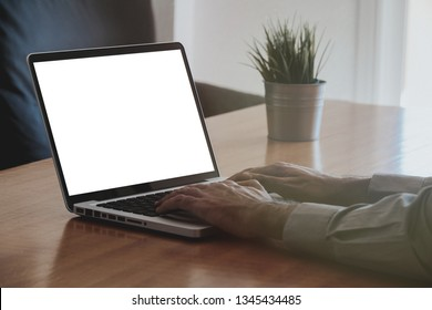 Man using a laptop computer with white blank screen.