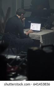 Man using laptop in dark room.