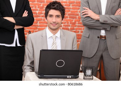 Man using a laptop flanked by people in suits