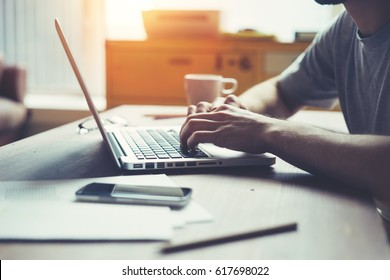 Man using laptop at his workplace. Loft office, researching new business strategy. Typing new letter. Intentional sun glare effect