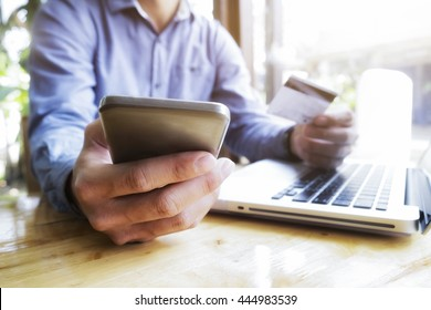 Man using laptop and mobile phone to online shopping and pay by credit card. Vintage tone, Retro filter effect, Soft focus, Low light.