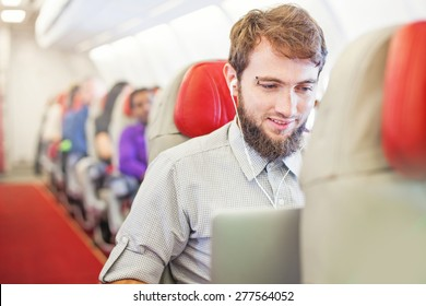 Man using laptop on board of aircraft