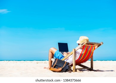 A man using laptop on the tropical beach on vacation. Technology for life concept.