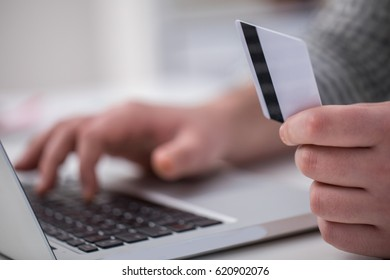 Man using laptop for online shopping in close up, part of