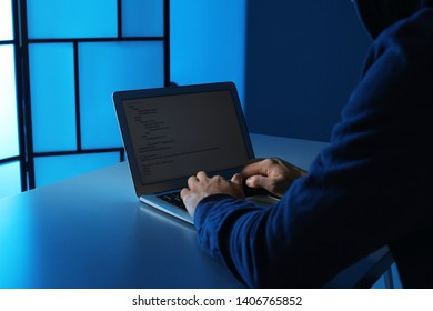 Man using laptop at table in dark room, closeup. Criminal offence