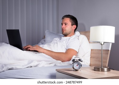Man Using Laptop While Relaxing On Bed