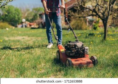 man using lawn mower outdoor.