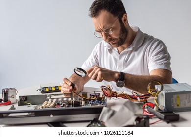 man using magnifier while holding wires in hand