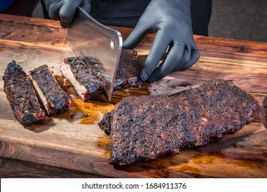 A man using a meat cleaver to chop up seasoned pork ribs
