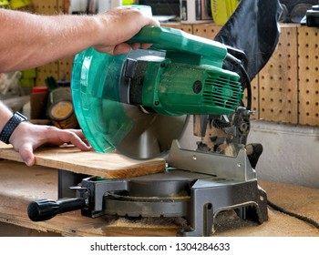 Man using mitre saw to cut wood