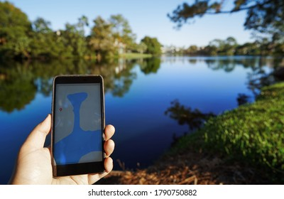 Man using mobile map app next to the lake. Smartphone with 5g connection