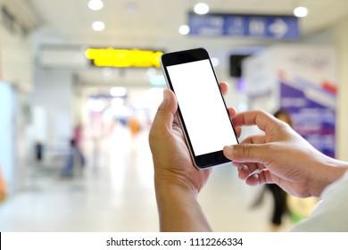 Man using mobile phone in airport terminal.