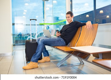 Man Using Mobile Phone In Airport Waiting Area