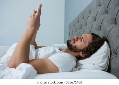 Man using mobile phone in bedroom at home