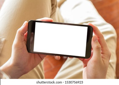 man using mobile phone with blank screen indoor, close up