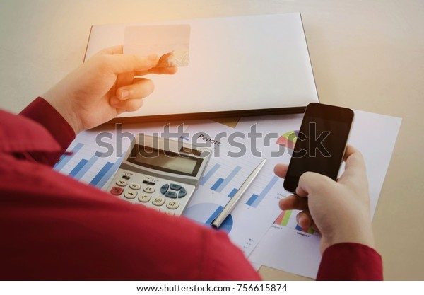 man using mobile phone and credit card for payment with calculator,  business strategy diagram and laptop computer on desk at home office, finance, technology, payment and shopping online concept