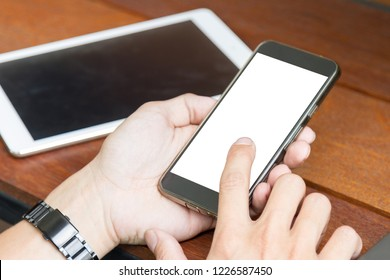 man using mobile phone and digital tablet on wooden table, outdoor scene