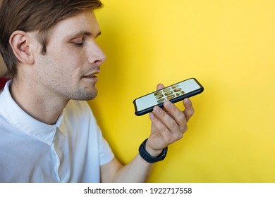 Man using mobile phone next to the yellow background. Social media screen. Clubhouse the voice-only social media app. Smiling male talking on the phone social platform built around drop-in audio chat