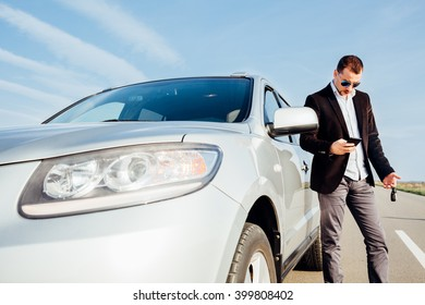 Man using a mobile phone next to the car
